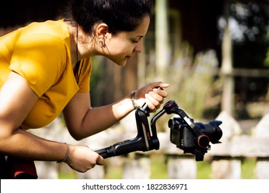 Young hispanic woman holding gimbal while making video outside. Technological concept