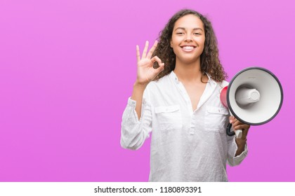 Young hispanic woman holding megaphone doing ok sign with fingers, excellent symbol