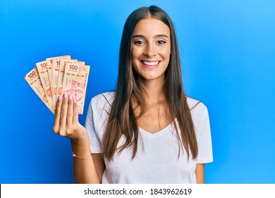 Young hispanic woman holding mexican pesos looking positive and happy standing and smiling with a confident smile showing teeth