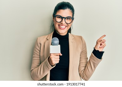 Young hispanic woman holding reporter microphone smiling happy pointing with hand and finger to the side
