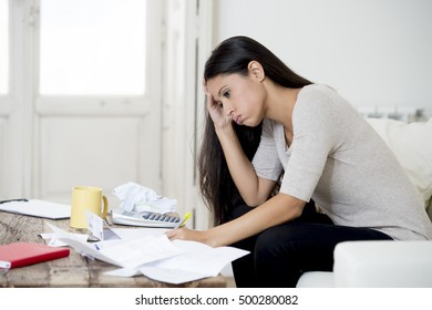 young hispanic woman at home living room couch calculating monthly expenses worried in stress with bank papers and documents in paying taxes , mortgage debt and cost of living concept