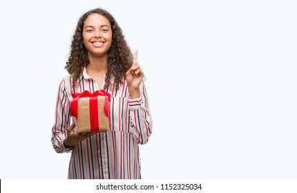 Young hispanic woman in love holding present surprised with an idea or question pointing finger with happy face, number one