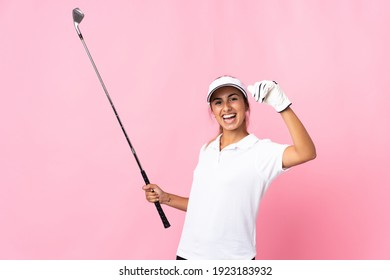 Young hispanic woman over isolated pink background playing golf and celebrating a victory
