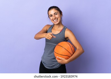 Young hispanic woman over isolated purple background playing basketball and pointing to the front