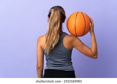 Young hispanic woman over isolated purple background playing basketball in back position