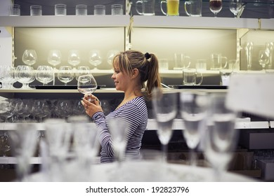 young hispanic woman shopping for furniture, glasses, dishes and home decor in store