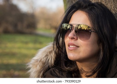 A young Hispanic woman smiling up close in a park in winter.