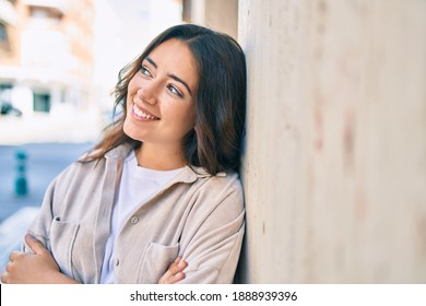 Young hispanic woman smiling happy leaning on the wall at the city.