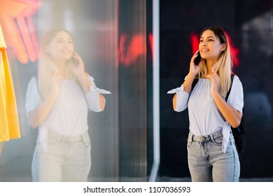 Young hispanic woman talking on mobile phone and window shopping