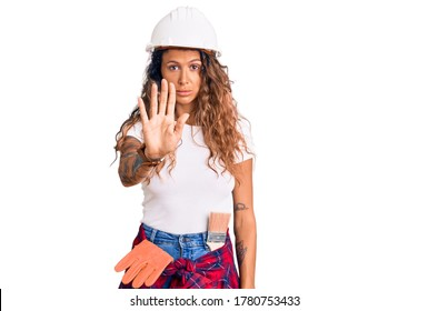 Young hispanic woman with tattoo wearing hardhat and builder clothes doing stop sing with palm of the hand. warning expression with negative and serious gesture on the face.