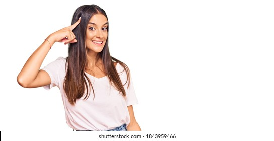Young hispanic woman wearing casual white tshirt smiling pointing to head with one finger, great idea or thought, good memory