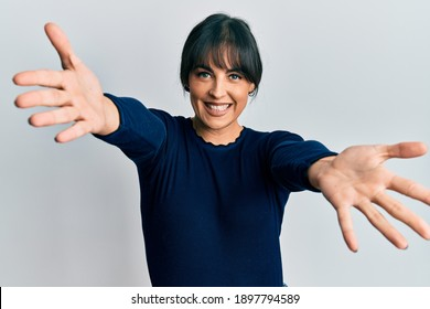 Young hispanic woman wearing casual clothes looking at the camera smiling with open arms for hug. cheerful expression embracing happiness.