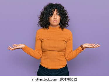 Young hispanic woman wearing casual clothes clueless and confused with open arms, no idea concept.