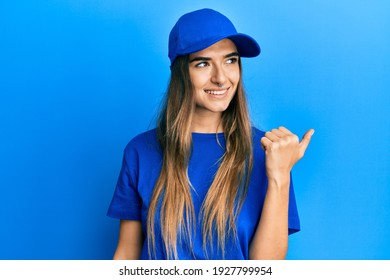 Young hispanic woman wearing delivery uniform and cap smiling with happy face looking and pointing to the side with thumb up.