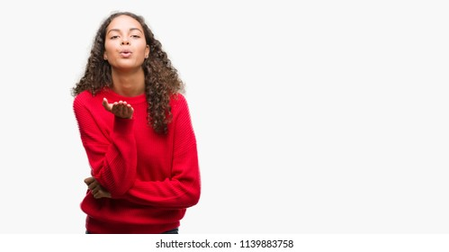 Young hispanic woman wearing red sweater looking at the camera blowing a kiss with hand on air being lovely and sexy. Love expression.
