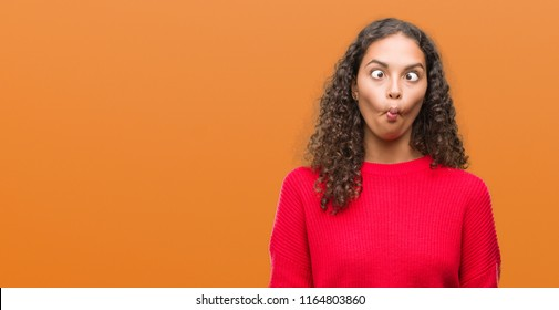 Young hispanic woman wearing red sweater making fish face with lips, crazy and comical gesture. Funny expression.