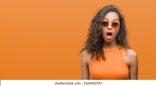 Young hispanic woman wearing summer outfit scared in shock with a surprise face, afraid and excited with fear expression