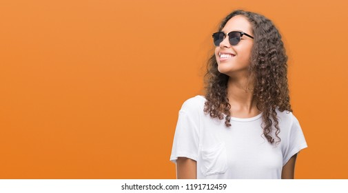 Young hispanic woman wearing sunglasses looking away to side with smile on face, natural expression. Laughing confident.