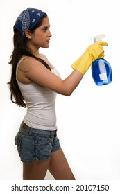 Young hispanic woman wearing yellow rubber gloves and headband holding a spray bottle with blue liquid