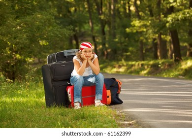 Young hitch-hiker girl standing on road side afternoon with bags