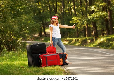 Young hitch-hiker girl standing on road side afternoon in forest with bags
