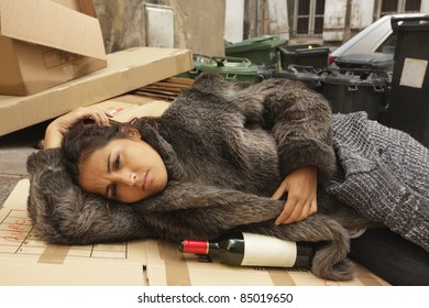 young hobo woman lying on city pavement with bottle of wine