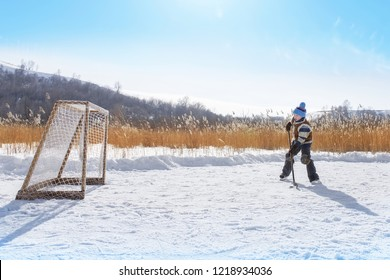 Young hockey boy trains alone on a frozen lake