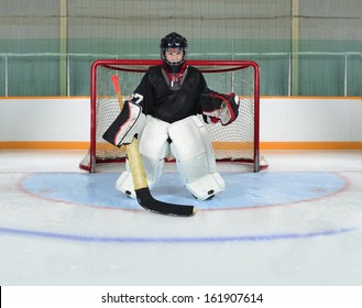 A Young Hockey Goalie Kid Protects his Net from a Goal