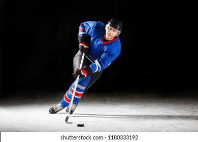 Young hockey player with stick and puck skating on rink in attack against dark background