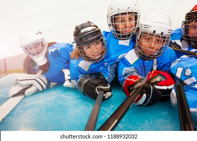 Young hockey players with sticks laying on ice