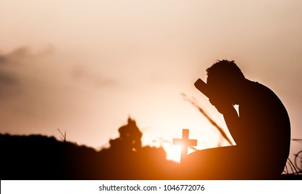 Young holding Bible book and praying to God with light sunset background. christian oncept