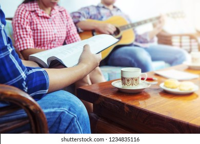 A young  holding bible while his friend plays guitar at home, Christian family, small group or house church worship concept