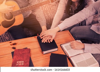 A young holding guitar joins hand and pray together over holy bible on wooden table  at home, Christian family, small group or house church worship concept