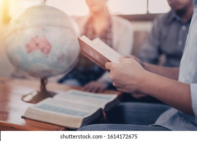 A young  holding and reads bible with his friend over blurred world globe and open bible on wooden table at home, Christian family, small group or house church worship concept, World mission ministry