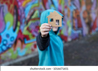 young homeless boy holding a cardboard house