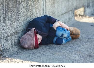 young homeless boy sleeping on the bridge, poverty, city, street