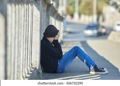 young homeless boy sleeping on the street, poverty, city