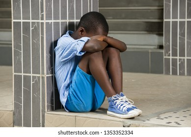 young homeless child who is afraid, is alone and has little hope for the future sitting against a building.