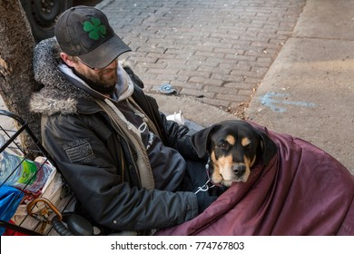 Young homeless man and his dog lying on street in sleeping bag, St. Hubert Street, Montreal, Quebec, Canada, November 20, 2015