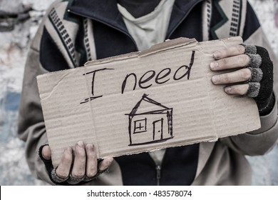 "Young homeless man holding sign ""I need home"""