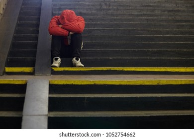 young homeless man sleeping on the street, poverty, city