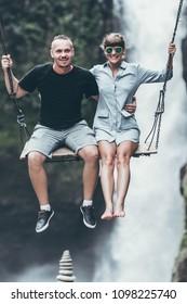 Young honeymoon couple swings in the jungle near the waterfall, Bali island, Indonesia. Ubud.