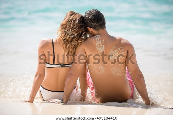 Young honeymooners are sitting on the coast of tropical beach. It has a sandy hand prints on the back.