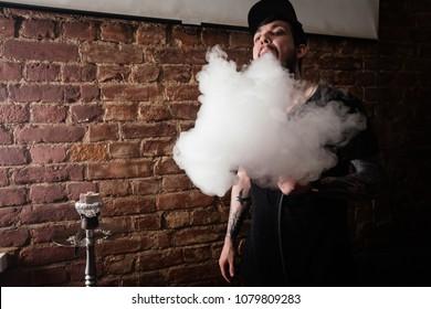 Young hookah maker with beard blowing huge clowds of smoke. Tatooed hookah server. Brick wall in the background.