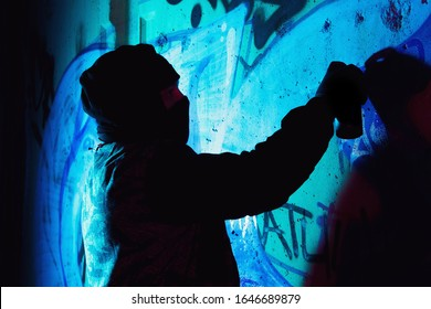 A young hooligan with a spray can stands against a concrete wall with graffiti paintings. Illegal vandalism concept. Street art