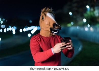 Young horse man sending sms with city park bokeh lights in background in night scene