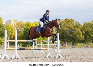 Young horse rider sportswoman on equestrian sport competition. Sport event background