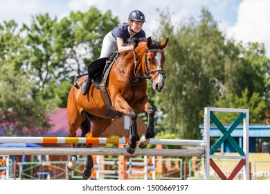 Young horse rider woman jumping over the obstacle on show jumping competition. Equestrian sport background