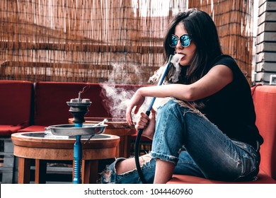 Young hot trendy girl smoking hookah outside