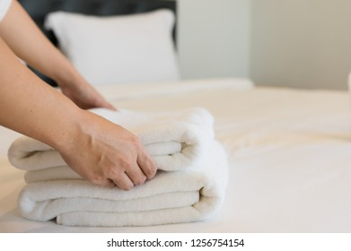 Young hotel maid putting soft towels, bedding and towels in a hotel cleaner was placed on a clean white blanket on the bed with a pillow in the bedroom the morning.
